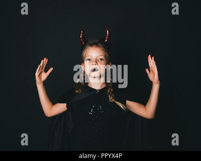 halloween girl with red horns in front of black background - Stock Photo