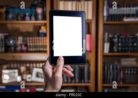 Womand hand holding e reader in front of bookshelves - Stock Photo