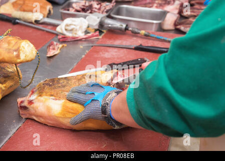 Close up of worker hands in the industrial process of cutting iberian ham - Stock Photo
