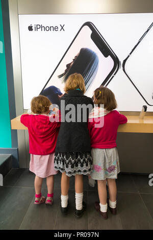 Three sisters girls / girl / child / kid / kids / child / children using an iPhone / i Phone X on display and for sale in an Apple store shop. UK (102 - Stock Photo