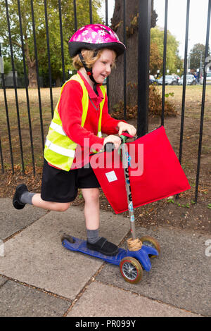 4 Year old child on scooter  / girl in her hi vis / high visibility vest jacket scootering home from school Reception class. UK. (102) - Stock Photo