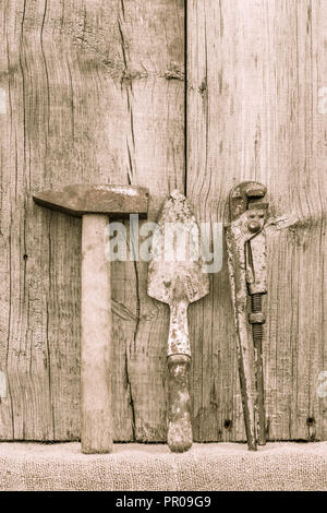 Old rusty hammer, trowel and adjustable wrench. Country tools. Rustic instruments, implements and farm equipment on wooden background. Vintage style - Stock Photo