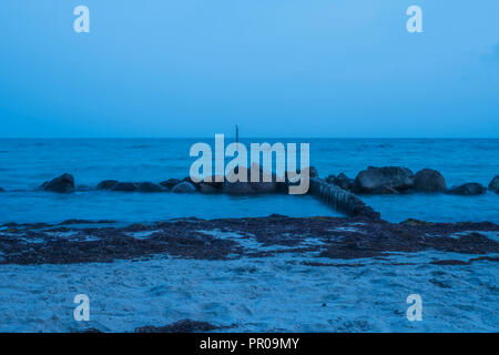 Rocks at the shore in blueish milky water after sunset during the blue hour at Rabylille Beach, Isle of Moen, Denmark, Scandinavia, Europe. - Stock Photo