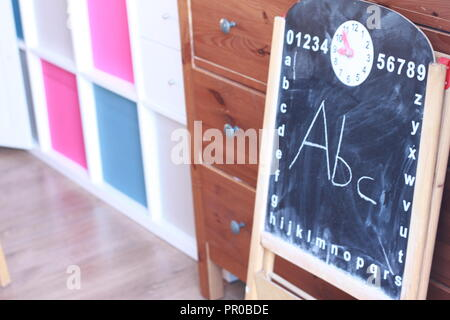 ABC written in chalk on a blackboard in a living room - Stock Photo