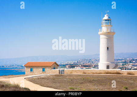 Old white lighthouse near the ancient ruins in Paphos Archaeological Park, Cyprus - Stock Photo