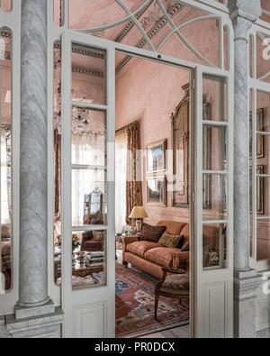 Pink and coral drawing room with marble columns and original frescoes cleaned and restored. Zeigler design carpet. - Stock Photo