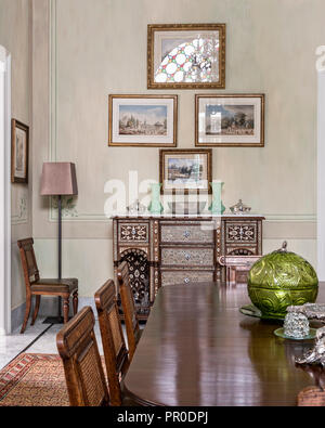 Antique dining table and 24 cane-backed chairs with inlaid Syrian chest dating from 1800's. - Stock Photo