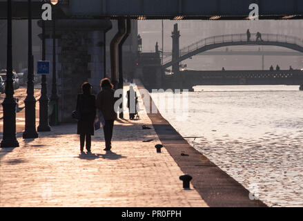 Paris Canal St. Martin - people strolling along the waterfront in the late afternoon sun, bridges in distance - Stock Photo