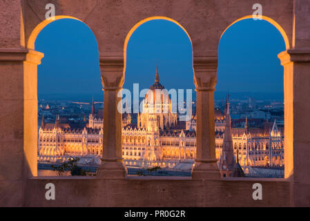 Hungarian Parliament at night, viewed from the columns and windows of the Fisherman's Bastion, UNESCO World Heritage Site, Budapest, Hungary, Europe - Stock Photo