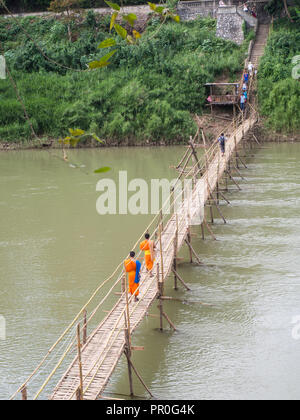 Orange-clad Buddhist monks crossing a bamboo bridge, Luang Prabang, Laos, Indochina, Southeast Asia, Asia - Stock Photo