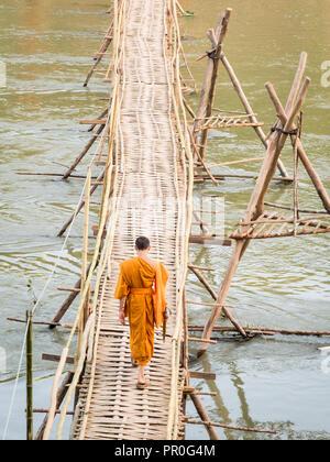 Orange-clad Buddhist monk crossing a bamboo bridge, Luang Prabang, Laos, Indochina, Southeast Asia, Asia - Stock Photo