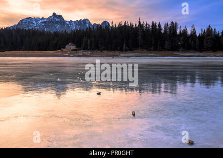 Colors of the sunset reflected on the icy surface of Lake Palu, Malenco Valley, Valtellina, Lombardy, Italy, Europe - Stock Photo