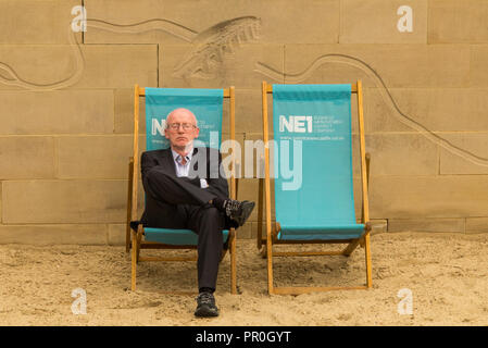 Businessman wearing a suit asleep in a deckchair on the man made beach on banks of the river Tyne Newcastle - Stock Photo