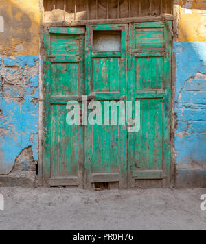 Closed green wooden grunge weathered abandoned door on dirty wall painted in yellow and blue colors - Stock Photo