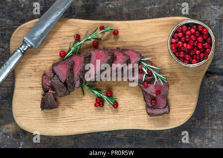 Sliced venison steak on wooden board with lingonberries - top view - Stock Photo