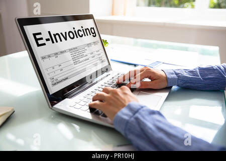 Close-up Of A Businesswoman's Hand Preparing E-invoicing Bill On Laptop Over Desk - Stock Photo