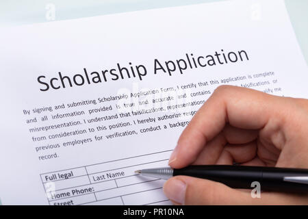 Close-up Of A Person's Hand Filling Scholarship Form With Pen - Stock Photo