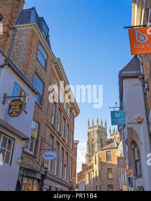 Low Petrergate, a street in York with its shops and the towers of York Minster in the background. - Stock Photo