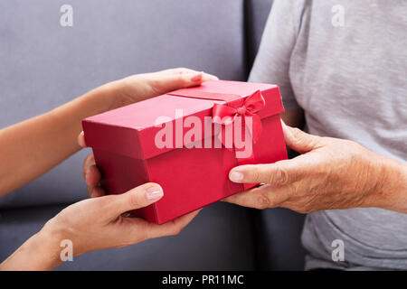 Close-up Of A Father And Daughter's Hand Holding Gift - Stock Photo