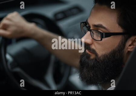 Attractive, elegant serious man drives a good car. Close up portrait, focus on facial expression. - Stock Photo
