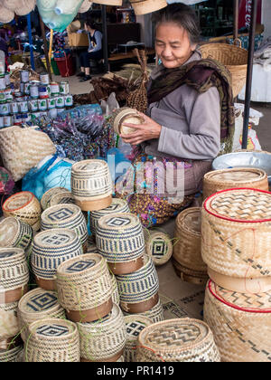 Woman selling baskets for sticky rice in central outdoor market, Luang Prabang, Laos, Indochina, Southeast Asia, Asia Stock Photo