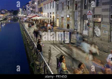 Navigli district at night with crowd on the banks of Naviglio Grande Canal, Milan, Lombardy, Italy, Europe - Stock Photo