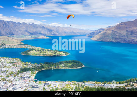 Aerial view of Queenstown, paraglider, Lake Wakatipu and The Remarkables mountains, Queenstown, Otago, South Island, New Zealand, Pacific - Stock Photo