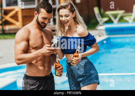 couple using smartphone and holding bottles of beer at poolside - Stock Photo