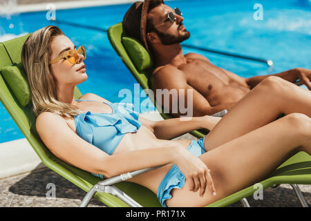beautiful young couple sunbathing on sunbeds at poolside - Stock Photo