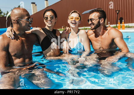 laughing multiethnic couples in sunglasses spending time in swimming pool - Stock Photo