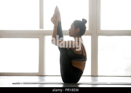 young attractive sporty woman doing boat pose grey studio