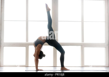 Young sporty attractive woman practicing yoga, One legged Wheel  - Stock Photo