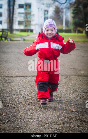 Funny toddler in red winter jumpsuit runs happily towards camera - Stock Photo