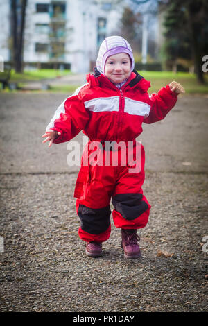 Cute toddler in red suit runs in the yard in winter - Stock Photo