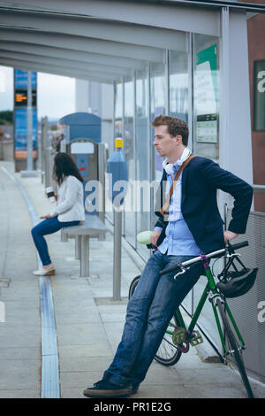 Businessman leaning against bicycle at railway station - Stock Photo
