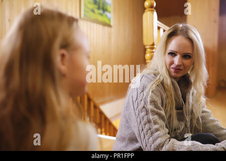 family warmed by the fireplace sitting on the couch - Stock Photo