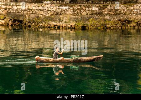 Young boy rowing canoe on Lake Toba Samosir Island Sumatra Indonesia - Stock Photo