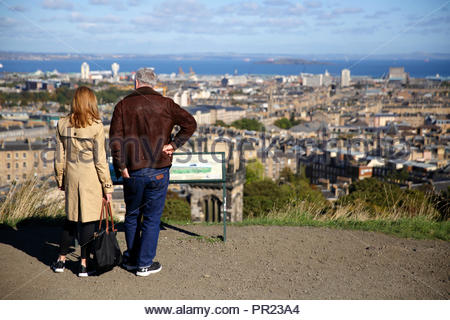 Tourists checking the Information board on Calton Hill Edinburgh Scotland, with a view over the city towards Leith and the Forth Estuary - Stock Photo
