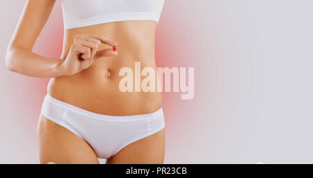 The pill is in the hand of the woman opposite the abdomen - Stock Photo