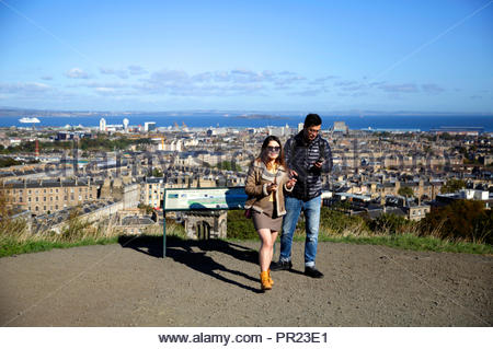 Tourists and Information board on Calton Hill Edinburgh Scotland, with a view over the city towards Leith and the Forth Estuary - Stock Photo
