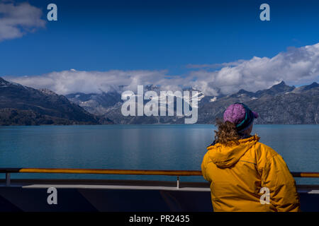 Glacier Bay, Alaska USA - Aug 17, 2018. A woman admiring a beautiful view of Glacier Bay with snow covered mountain, blue sky and white clouds from th - Stock Photo