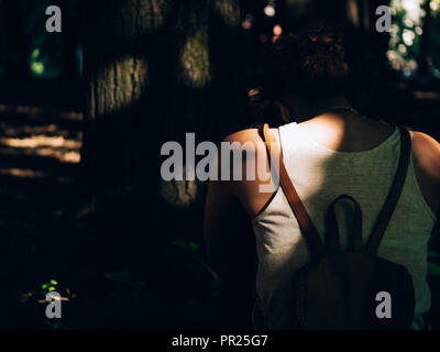 A black girl from the back with a backpack rucksack with her head pointing down in front of a tree with sun rays shining through leaves very cozy fear - Stock Photo