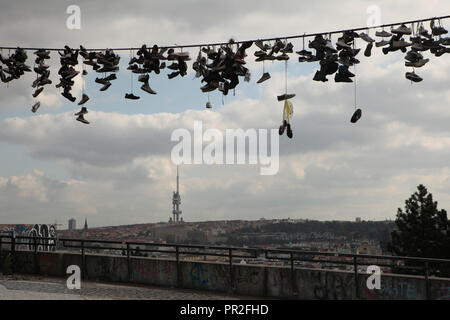 Old boots hang on the electrical cable in Letná Park (Letenské sady) in Prague, Czech Republic. The panorama of Prague with the Žižkov Television Tower (Žižkovský vysílač) is seen in the background. According to local legend, teenagers throw shoes on the cable, when they lose their virginity. - Stock Photo