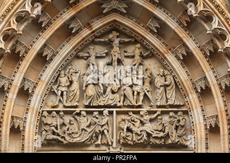 Tympanum of the main portal of Saint Vitus' Cathedral in Prague Castle in Prague, Czech Republic. The Crucifixion, the Disrobing of Christ and the Lamentation of Christ are depicted in the relief by Czech sculptor Karel Dvořák (1949). - Stock Photo