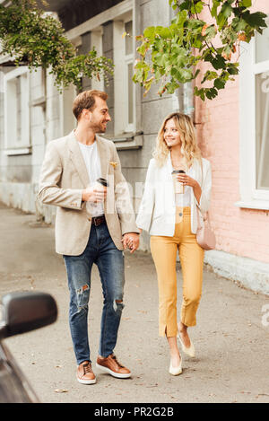 cheerful couple in autumn outfit holding hands, looking at each other and walking on street with disposable coffee cups - Stock Photo