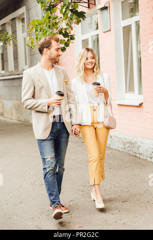 smiling couple in autumn outfit holding hands and walking on street with disposable coffee cups - Stock Photo