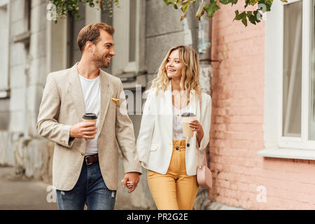 smiling couple in autumn outfit holding hands, looking at each other and walking on street with disposable coffee cups - Stock Photo