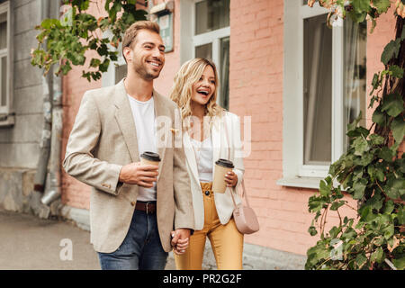 laughing couple in autumn outfit holding hands and walking on street with disposable coffee cups - Stock Photo
