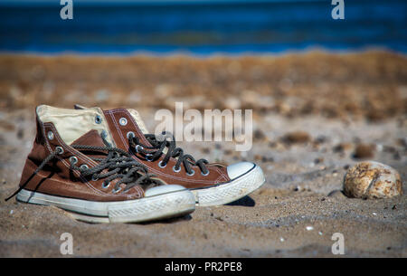 A pair of old worn brown canvas style retro basketball sneakers (one shoe in focus, the other in soft focus) on the sand at the beach with the water i - Stock Photo