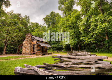An old log and stone cabin in the green woods with an old wooden fence in the foreground and a grey sky - Stock Photo